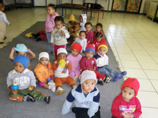 Babies in the Infant Day Care Centre have warm hats knitted by Dilys Marais
